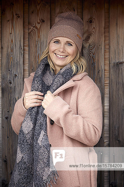 Portrait of smiling woman in winter clothes at wooden wall