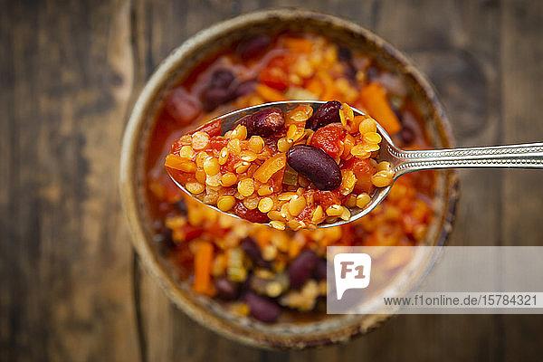Löffel veganer Chili mit roten Linsen  Stangensellerie  Kidneybohnen  Tomaten und Karotten