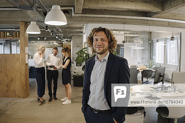 Porträt eines selbstbewussten Geschäftsmannes im Amt mit Kollegen im Hintergrund