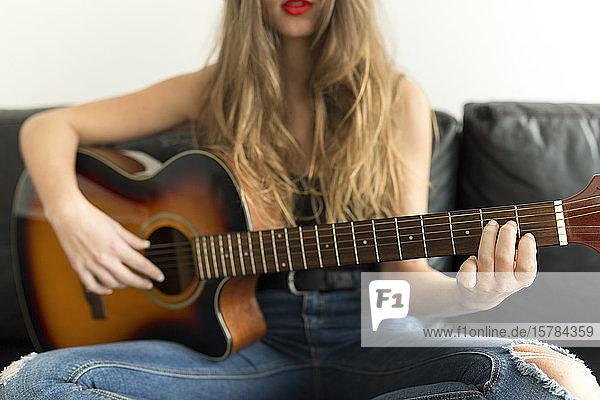 Schrägansicht einer jungen Frau  die auf einer Couch sitzt und Gitarre spielt