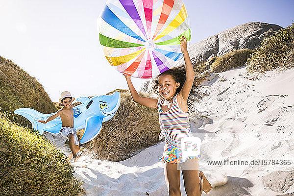 Glückliche Jungen und Mädchen rennen durch die Dünen zum Strand Glückliche Jungen und Mädchen rennen durch die Dünen zum Strand