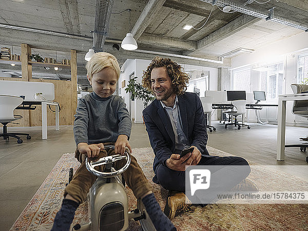 Smiling businessman with son on toy car in office