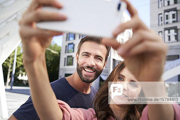 Glückliches Paar  das sich in der Stadt ein Selfie gönnt