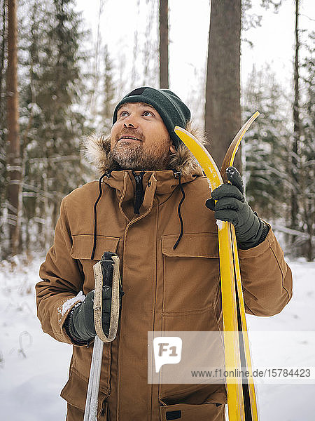 Portrait of man with skis looking up