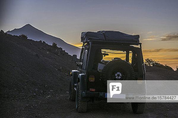Spanien  Teneriffa  Rückansicht eines Geländewagens im Teide-Nationalpark bei Sonnenuntergang