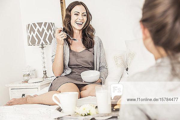 Porträt einer lachenden Frau beim Frühstück mit ihrer Tochter im Bett
