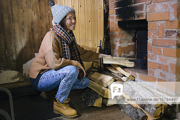 Smiling woman near the fireplace at home