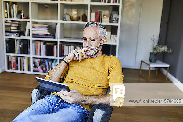 Relaxed mature man at home using tablet