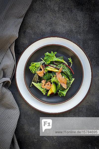 Teller grüner Salat mit Feldsalat  Rucola  Spinat  rotem Blattsalat  Rote-Bete-Blättern  Avocado  Lachsfleisch und Balsamico-Essig