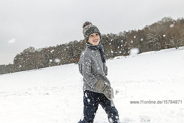 Portait of happy boy in winter landscape with snowfall