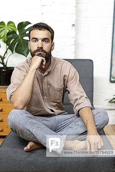 Junger Mann sitzt zu Hause im Schneidersitz auf der Couch