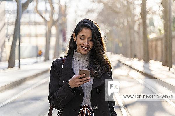 Lächelnde junge Frau mit Smartphone auf Straßenbahnlinie