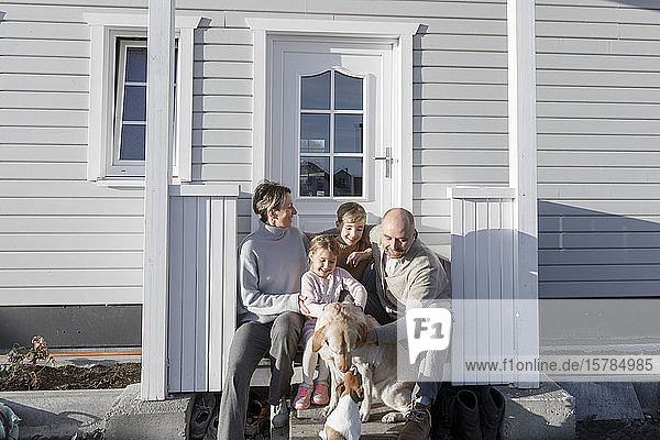 Glückliche Familie mit zwei Kindern und zwei Hunden  die vor ihrem Haus sitzen