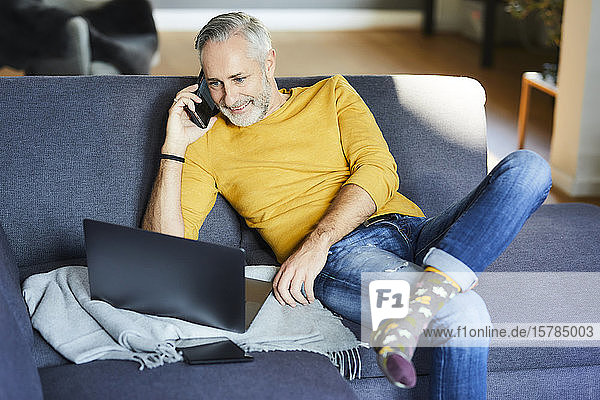 Mature man using cell phone and laptop on couch at home