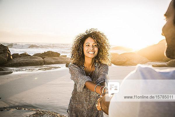 Glückliches Paar hält sich bei Sonnenuntergang am Strand an den Händen