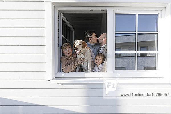 Glückliche Familie mit zwei Kindern und einem Hund am geöffneten Fenster ihres Hauses