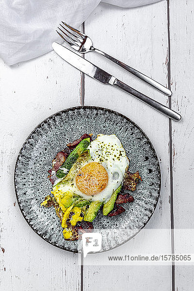 Fried egg with bacon  sliced avocado and Parmesan cheese