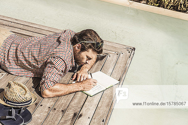 Man lying next to a pool writing in a notebook