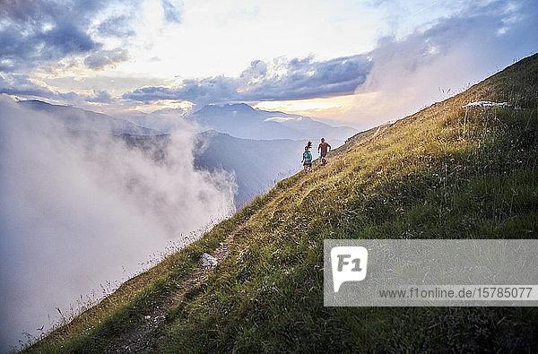 Mann und Frau laufen in den Bergen bergauf