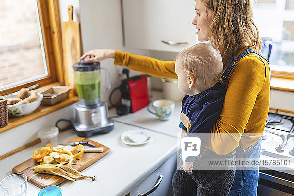Woman in the kitchen preparing healthy smoothie and holding her baby son