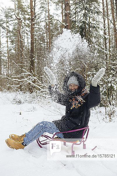 Glückliche Frau sitzt auf Schlitten und wirft im Winterwald Schnee in die Luft