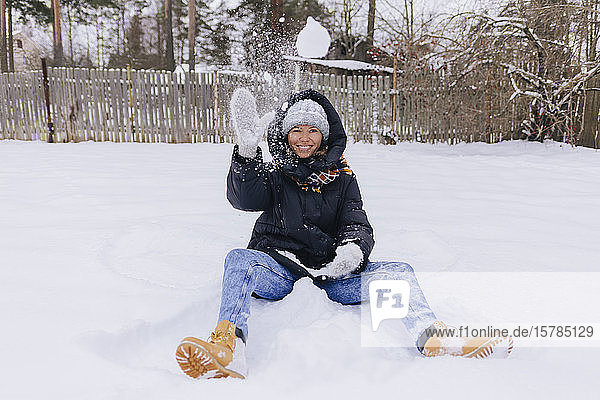 Happy woman sitting on snow field playing with snowballs