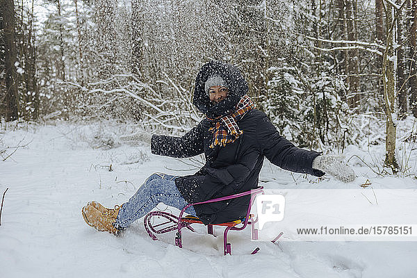 Smiling woman sitting on sledge throwing snow into the air in winter forest