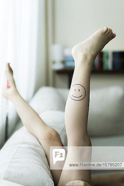 Mädchenbein mit gemaltem Smiley-Gesicht