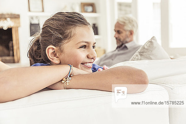 Smiling girl on couch in living room with father in background