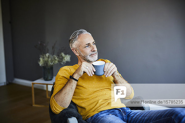 Relaxed mature man at home with cup of coffee