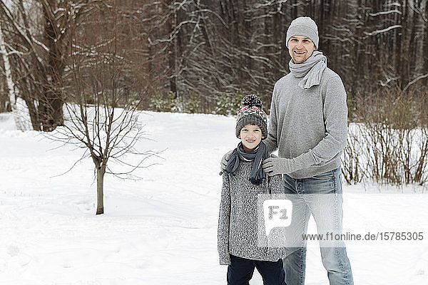 Portrait of happy father with this son in winter landscape