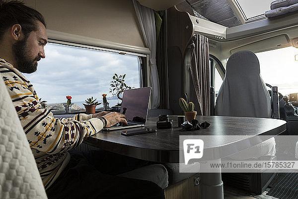 Mann arbeitet am Laptop in seinem Wohnwagen  Es Mercadal  Menorca  Spanien
