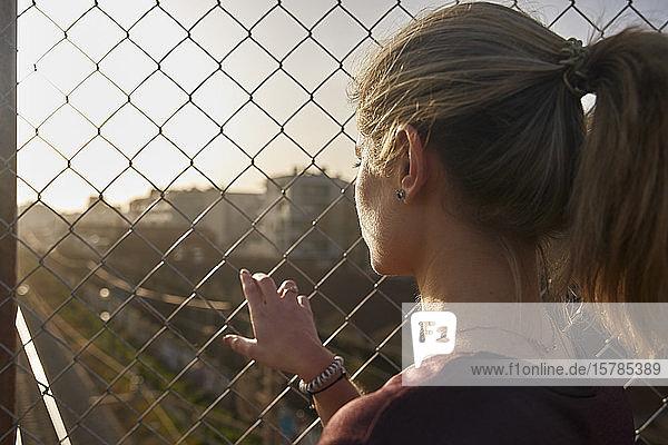 Sportliche junge Frau schaut durch einen Zaun