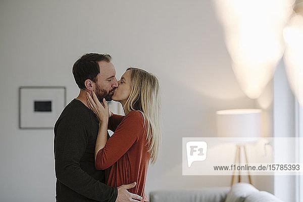 Glückliches Paar umarmt und küsst sich in ihrem gemütlichen Heim