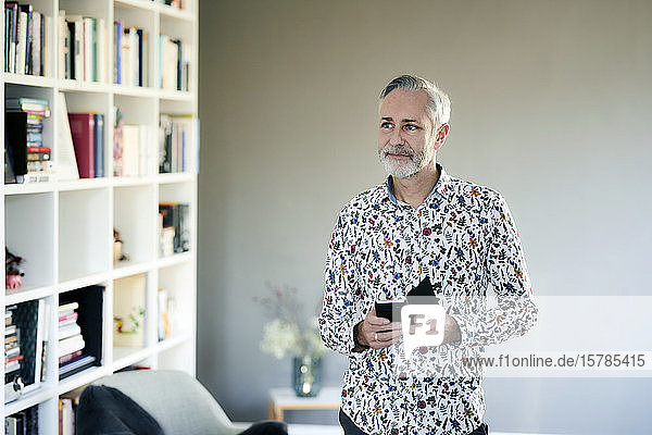 Mature man with cell phone wearing patterned shirt at home