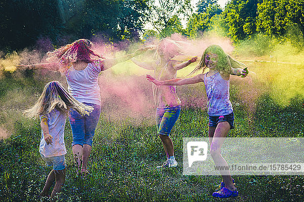 Group of two women and two girls celebrating Festival of Colours on a meadow