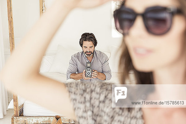 Bearded man sitting on bed with old-fashioned camera with woman in foreground