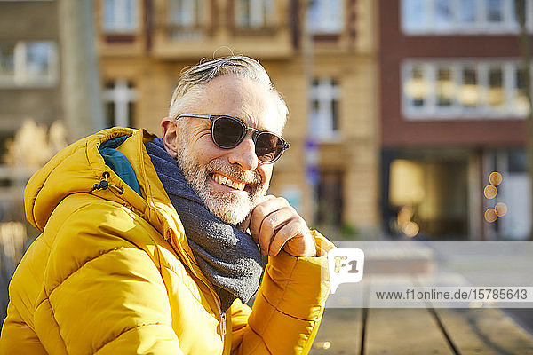 Portrait of smiling mature man wearing sunglasses in the city