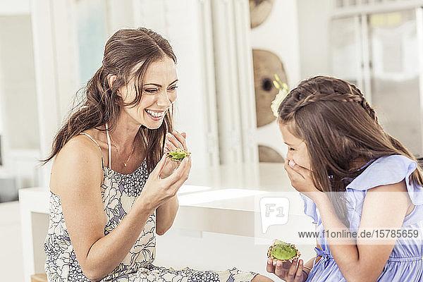 Glückliche Mutter und Tochter essen zu Hause Avocadobrot