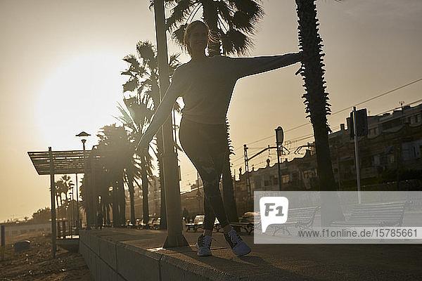 Junge Frau balanciert bei Sonnenuntergang auf der Strandpromenade
