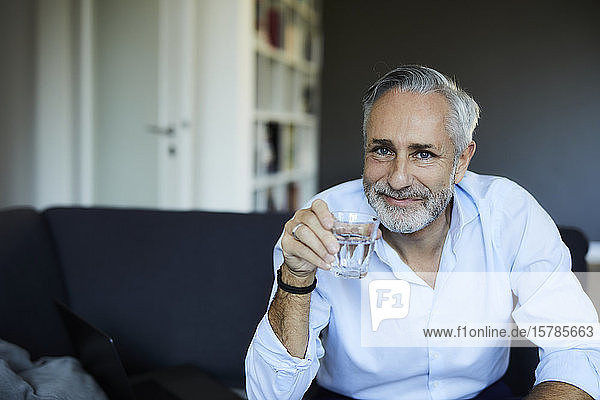 Smiling mature man drinking glass of water on the sofa at home