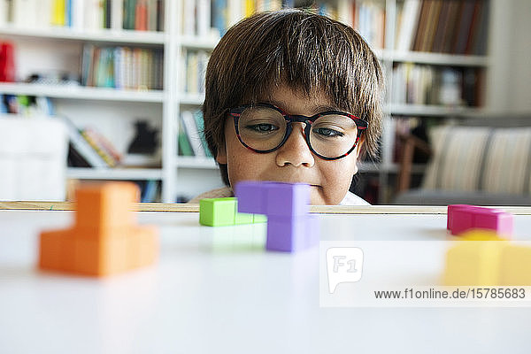 Portrait of little boy with glasses playing with building blocks at home