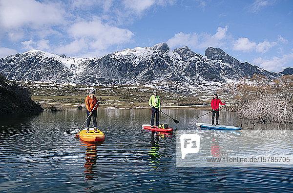 Drei Personen stehen beim Paddel-Surfen auf  Leon  Spanien