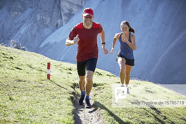 Man and woman running uphill in the mountains