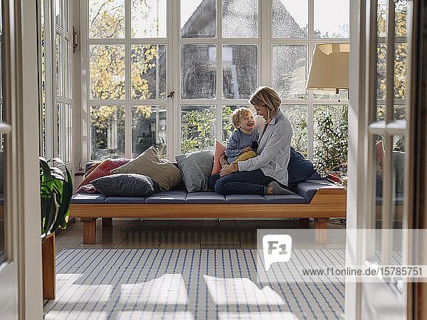 Glückliche Mutter und Sohn im Sonnenzimmer zu Hause