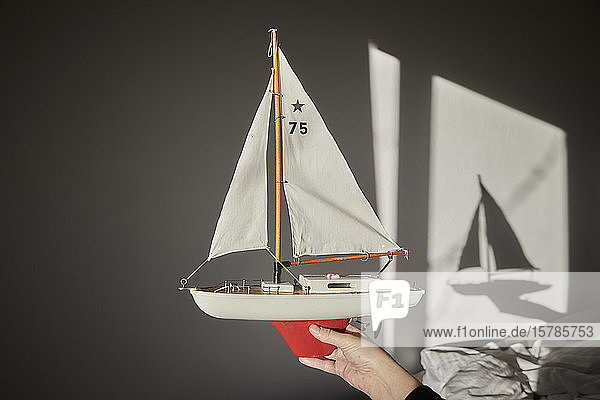Hand holding model sailboat
