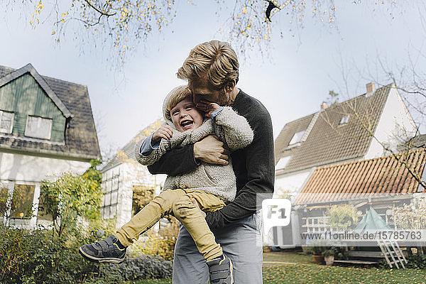 Glücklicher Vater spielt mit Sohn im Garten