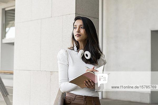Junge Frau macht Notizen im Freien