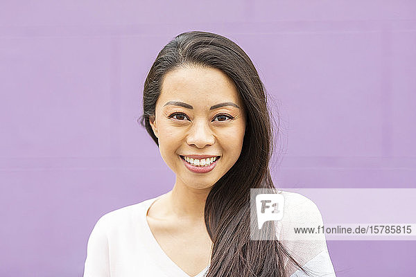 Bildnis einer glücklichen Frau mit langen braunen Haaren vor violettem Hintergrund