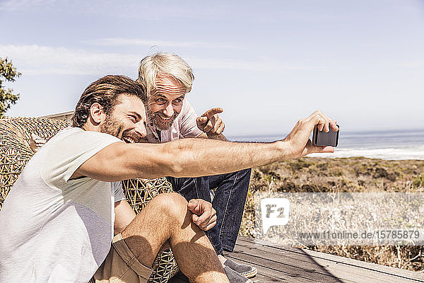 Father and adult son taking a selfie and having fun together on a terrace at the sea